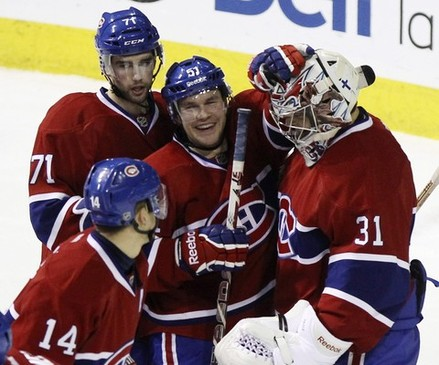 Montreal Canadiens goalie Carey Price is congratulated on his win by teammates following NHL hockey overtime shootout action against Pittsburgh Penguins in Montreal